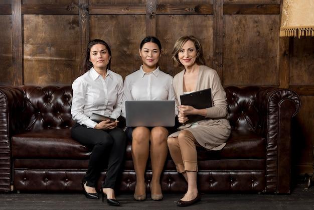 Frauen auf der couch mit modernen geräten