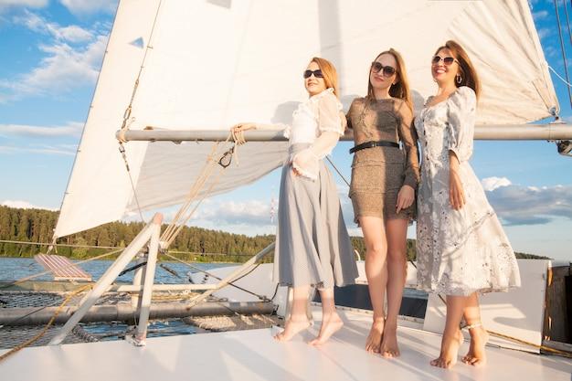 Frauen auf einer yacht, gegen die segel des himmels und des meeres. das konzept des segelns und eines urlaubs am meer.