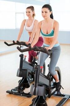Frauen auf heimtrainern. zwei schöne junge frauen in sportkleidung, die auf fitnessfahrrädern trainieren