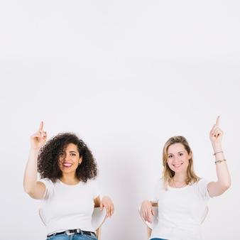 Frauen auf stühlen zeigen nach oben