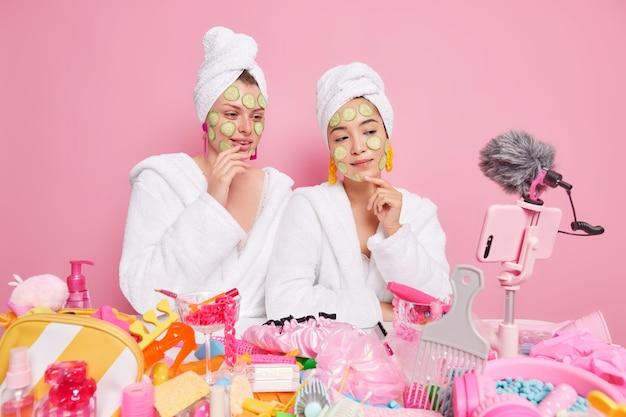 Frauen beauty blogger tragen gurkenscheiben auf das gesicht auf, um die haut mit feuchtigkeit zu versorgen ratschläge zur pflege des teints in weißen bademänteln verschiedene kosmetikprodukte verwenden