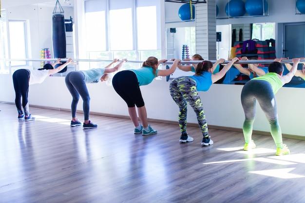Frauen beim dehnen mit dem metallgeländer im fitnessstudio