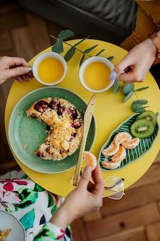 Frauen beim tee mit pflaumenstreuselkuchen