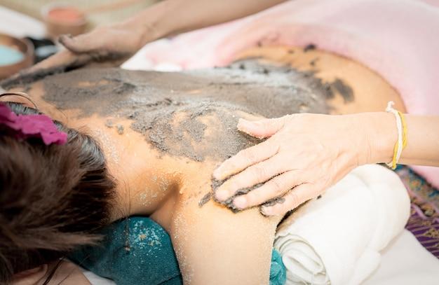 Frauen bekommen in spa lehmpeeling auf den rücken