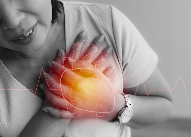 Frauen benutzen die hand, um mit schmerzen auf der brust zu lochen und leiden an herzkrankheiten mit herzform-grafikdesign auf der obersten schicht. konzept des st-erhöhten myokardinfarkts.
