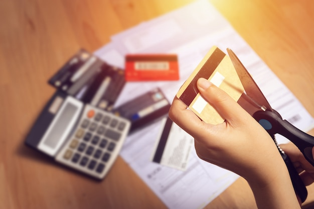 Frauen benutzen eine schere, um kreditkarten in der hand zu schneiden