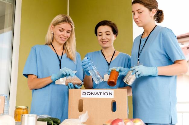 Frauen bereiten schachtel mit lebensmittelspende vor