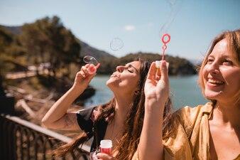 Frauen blasen und fangen Blasen