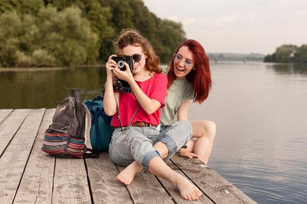 Frauen bleiben am dock und machen fotos