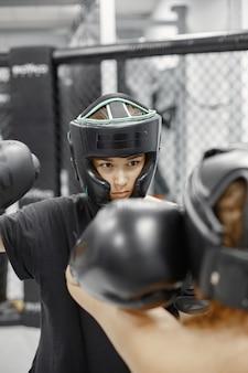 Frauen boxen. anfänger im fitnessstudio. dame in schwarzer sportbekleidung.