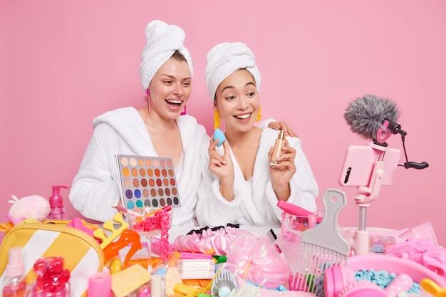 Frauen creat beuth blog-inhalte über kosmetikprodukte sprechen hält bunte lidschatten-palette und foundation gibt make-up- und hautpflegetipps für follower live-streaming-video aufnehmen