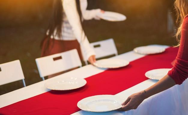 Frauen decken den tisch zum abendessen