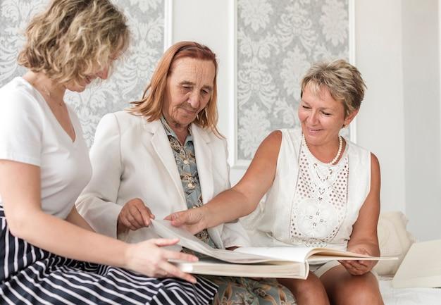 Frauen der multi generation, die altes fotoalbum während des sitzens auf sofa schauen