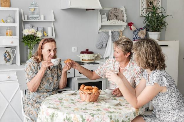 Frauen der multi generation, die hörnchen mit kaffee während des frühstücks genießen
