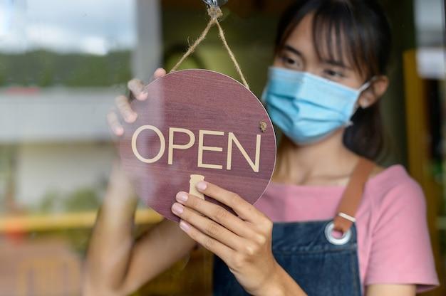 Frauen der neuen generation, die eine maske tragen, um kleine geschäfte in der coffeeshop-theke zu machen eröffnung eines shops