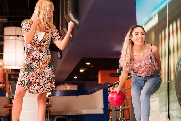 Frauen der niedrigen ansicht, die bowlingspiel spielen