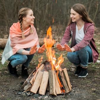 Frauen, die am lagerfeuer wärmen
