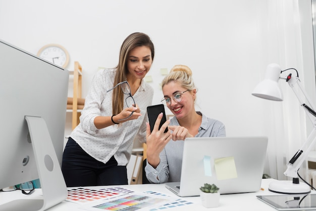 Frauen, die am telefon büro betrachten