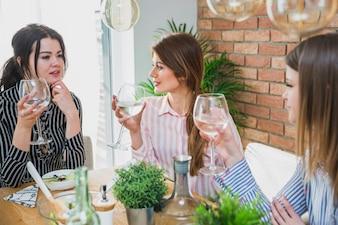 Frauen, die am Tisch hält Gläser sitzen