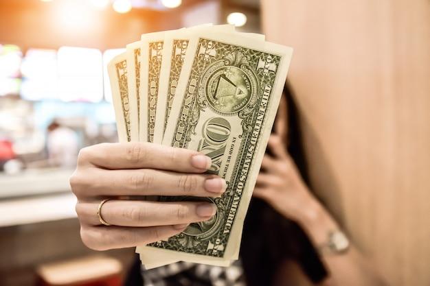 Frauen, die an hand dollar halten