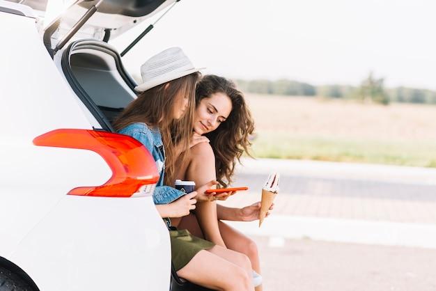Frauen, die auf autokofferraum auf feldhintergrund sitzen