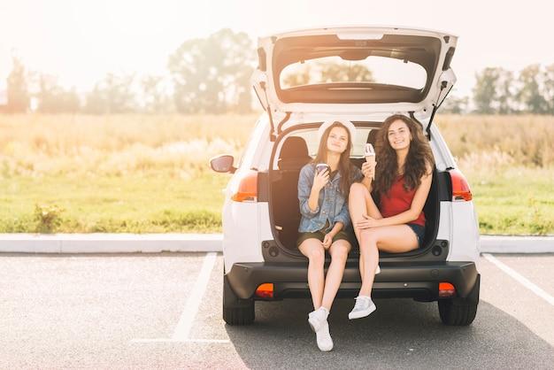 Frauen, die auf autokofferraum mit eiscreme sitzen