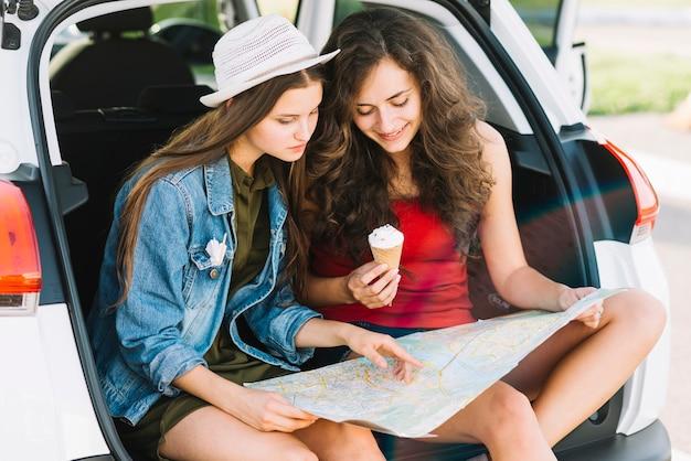 Frauen, die auf autokofferraum mit karte sitzen