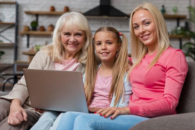 Frauen, die auf couch im wohnzimmer lächeln und sitzen