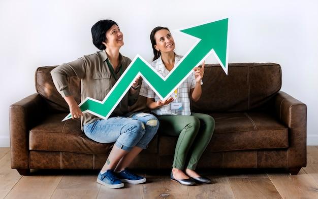 Frauen, die auf couch sitzen und statistikenikone halten