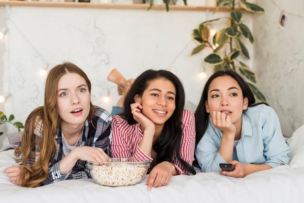 Frauen, die auf dem bett liegen und fernsehen