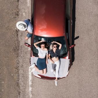 Frauen, die auf der autohaube und dem männlichen freund stehen nahe dem auto liegen