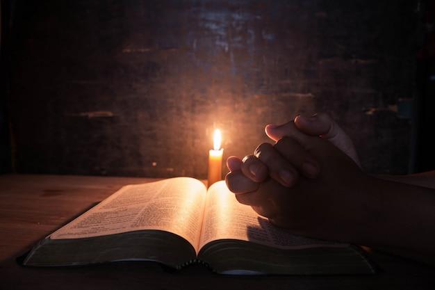 Frauen, die auf der bibel im selektiven fokus der hellen kerzen beten.