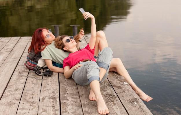 Frauen, die auf dock liegen und selfie machen