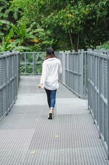 Frauen, die auf einer eisenbrücke im park aufwerfend stehen