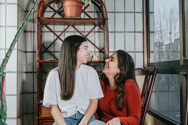 Frauen, die auf einer modernen flachen galerie in der stadt miteinander lächeln