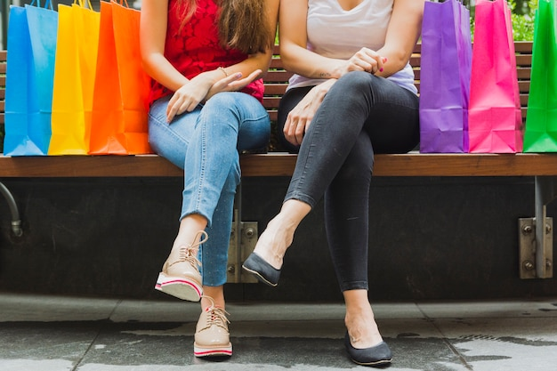 Frauen, die auf holzbank mit einkaufstaschen sitzen