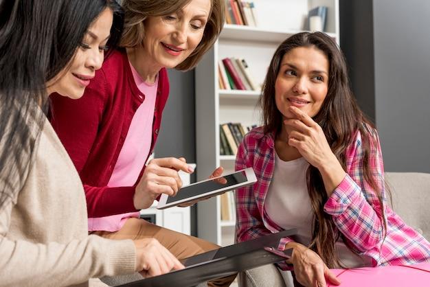Frauen, die auf klemmbrett und tablette schauen