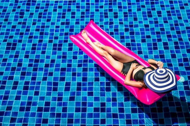Frauen, die auf rosa aufblasbaren matratzen sich entspannen und liegen.