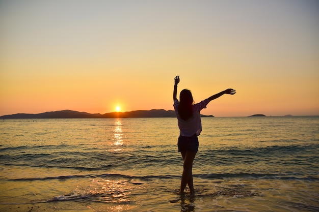 Frauen, die auf strand am seesonnenunterganghintergrund am abend der goldenen stunde stehen.