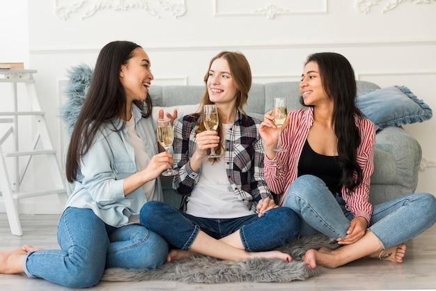 Frauen, die auf trinkendem champagner des bodens sitzen
