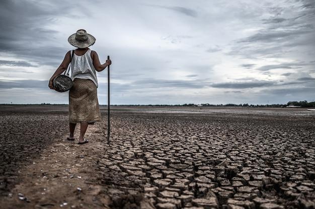 Frauen, die auf trockenem boden und fischereiausrüstung, globaler erwärmung und wasserkrise stehen
