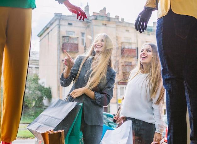 Frauen, die außerhalb des shops stehen, finger auf fensteranzeige zeigend