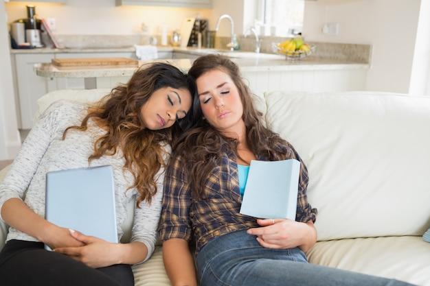 Frauen, die beim halten von tablet-computern schlafen