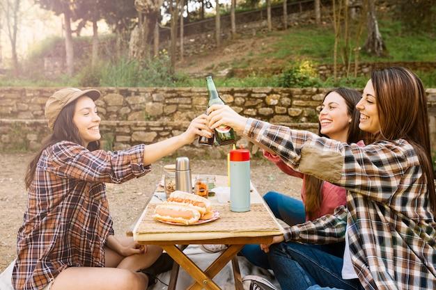 Frauen, die bier in der natur trinken