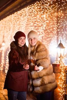 Frauen, die champagner genießen. outdoor-porträt von damen auf licht