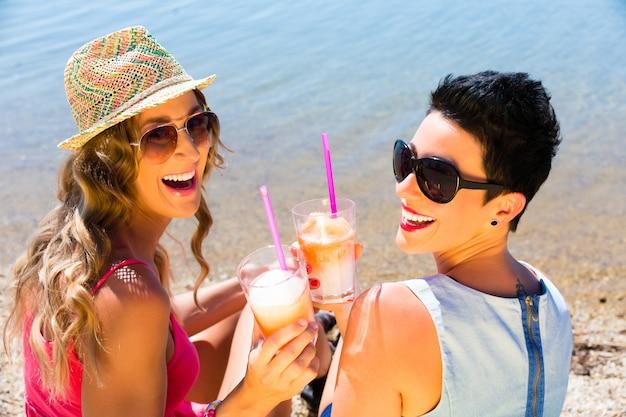 Frauen, die cocktails am strand trinken