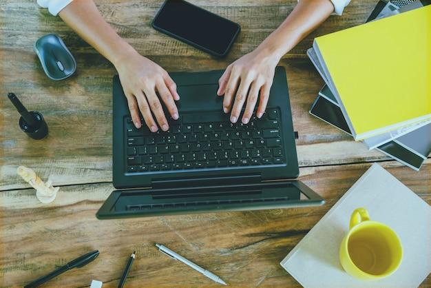 Frauen, die das arbeiten an der hölzernen tabelle arbeitet mit einem laptop sitzen