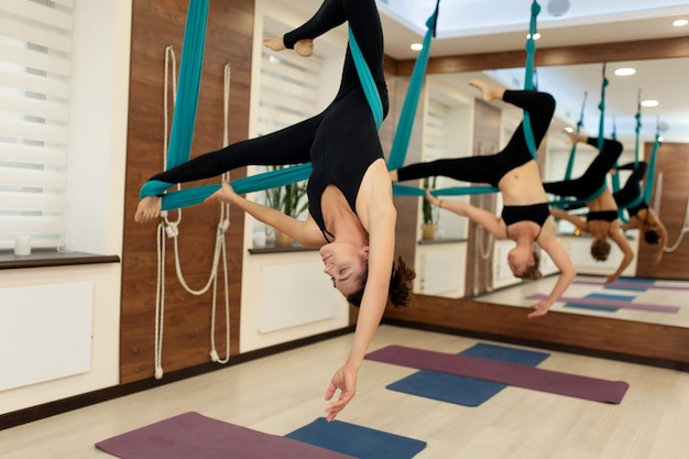 Frauen, die das hängen umgedreht in einer hängematte ausdehnen.