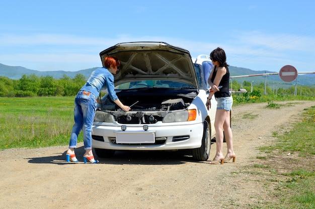 Frauen, die das kaputte auto mit geöffneter motorhaube auf einer landstraße reparieren