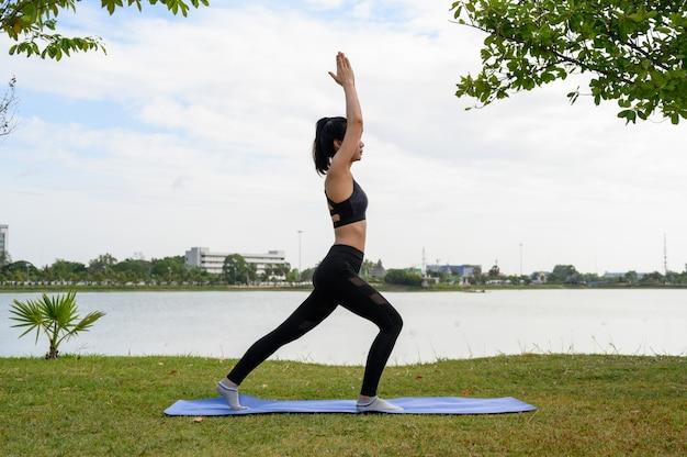 Frauen, die das schwarze, übende yoga für gesundheit am park tragen.